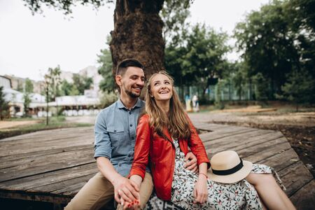 Young cheerful guy and girl spend time together sitting near a tree in the park. Love story