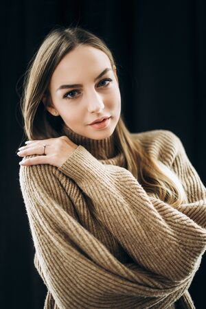 Portrait of a beautiful blue-eyed blonde with long hair in a beige pullover on a black background