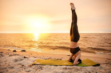 Yoga by the sea at sunset. The girl practices yoga near the sea, she stands on her head