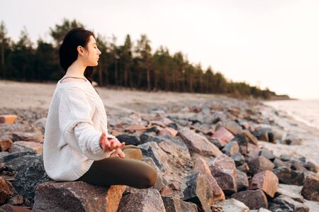 Girl is meditating sitting in lotus position on the stones near the sea at sunset