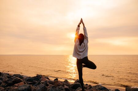 A girl practices yoga by the sea during a beautiful sunset. She stands in a tree pose