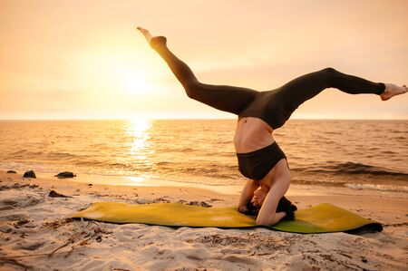 A girl practices yoga by the sea during a beautiful sunset. Fitness and healthy lifestyle