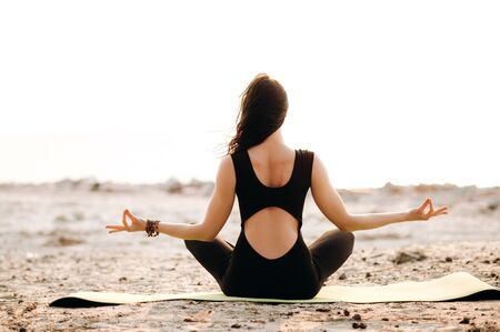 A girl practices yoga on nature. She is sitting in a lotus position and meditating