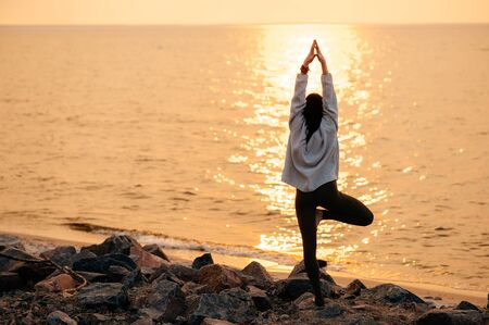 Yoga by the sea at sunset. The girl practices yoga near the sea, she stands in a tree pose