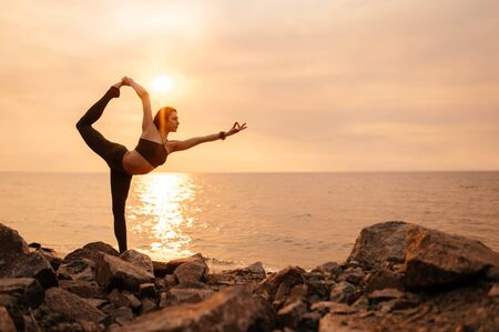 Yoga at sunset. A girl practices yoga by the sea during a beautiful sunset. Fitness and healthy lifestyle