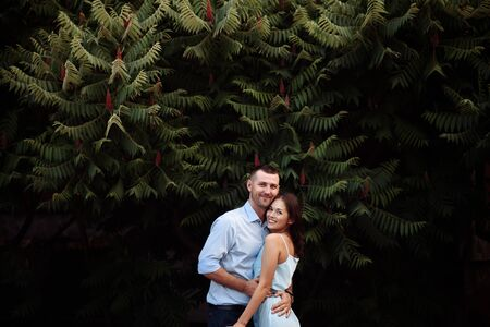Portrait of a happy couple in love. Stylishly dressed guy and girl hugging and smiling on nature