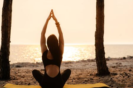A girl practices yoga by the sea during a beautiful sunset. She is sitting in lotus position and meditating