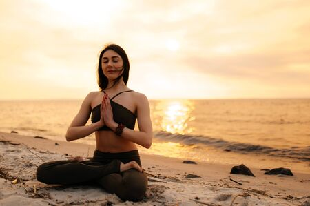 A young girl sits in a lotus position on the seashore at sunset. Girl practices yoga by the sea