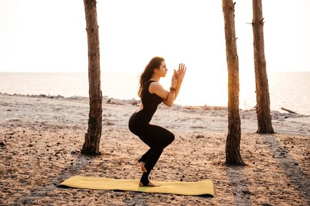 Attractive girl in a fitness suit does fitness on the nature near the sea at sunset