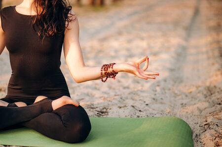 Meditating girl on the nature. She is sitting in a lotus position. Close-up photo