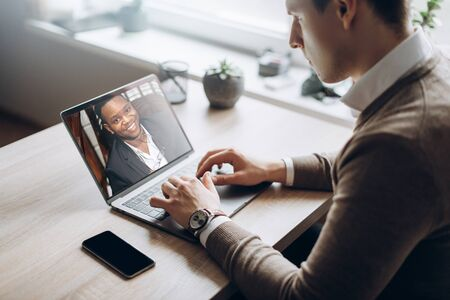 Business partners communicate via video using laptop. The guy talks with his business partner Afro-American appearance about plans and strategy. Distant work