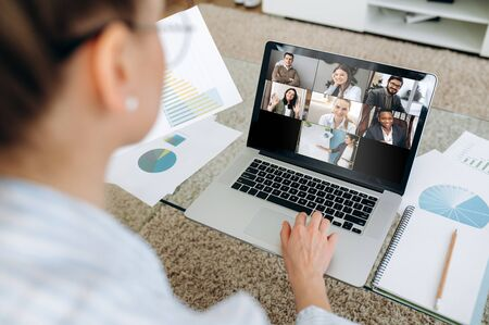 Business team working from home in a video conference. The back view of a girl who communicates online by video conference with her work colleagues using a laptop. Zoom conference Banque d'images