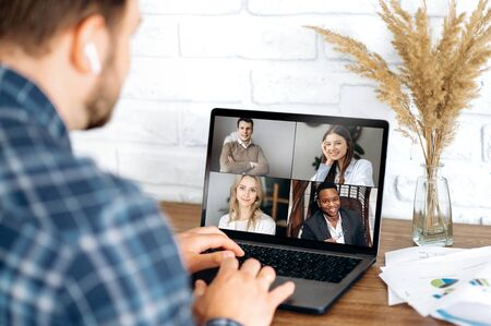 Online business meeting in video conference in the zoom app. A young attractive guy communicates with his colleagues on a video call using a laptop. Distant work at home Foto de archivo