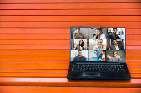 Virtual meeting online. Video conference by laptop. Online business meeting. On the laptop screen, people who gathered in a video conference to work or learning on-line. The laptop is on a orange bench Foto de archivo