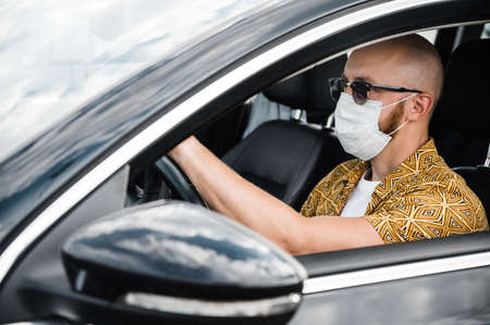 Quarantine. A man wearing a protective medical mask and sunglasses drives in his car to the shop during the quarantine of coronavirus