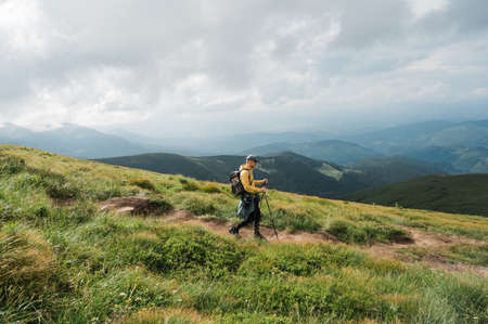 A hikers man in a hiking gear and with hiking sticks goes down the mountain along the path