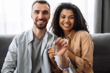 Joyful couple in a new apartment or house, looking at the camera and smiling. Happy african american woman and caucasian man sitting at the couch, hold a key in arms from their new home, moving day