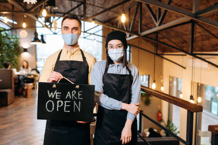 We are OPEN. Two friendly multiracial waiters wearing protective masks. Attractive caucasian guy and beautiful asian girl in black aprons stand inside a restaurant, cafe or bar and showing signboard