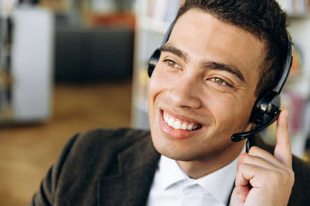 Close-up portrait of smiling hispanic male consultant, operator of call center sitting at the desk, wearing headset. Young adult employee is talking with people, support service concept