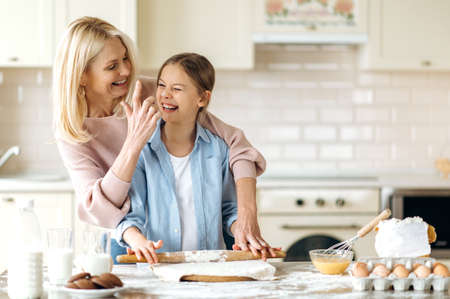 Cheerful mom or grandma and her pretty little daughter or granddaughter spend time together at the kitchen. They cook together a pie, indulge in flour, laugh and have fun Stock Photo