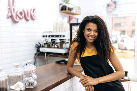Photo of a friendly waitress wearing uniform, african american female barista, with curly hair in black apron standing near the bar counter, looks and smiles at the camera