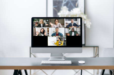 Online lesson, distance learning. On the computer screen is many different multiracial people and a teacher who conducts an online lecture for students using a video conference
