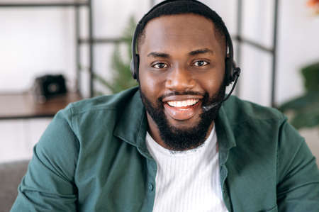 Close-up portrait of an attractive confident bearded African American operator of call center or business leader. Black businessman in headset and casual shirt looks at the camera and friendly smiling