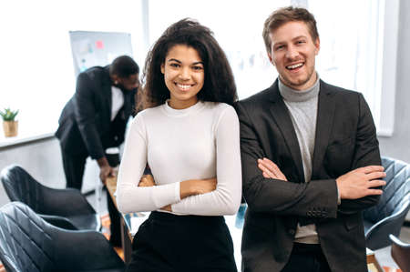 Portrait of young adult business partners are standing with cross hands in modern office,. Happy confident multiethnic colleagues in formal wear looking at the camera, smiling, teamwork concept Imagens
