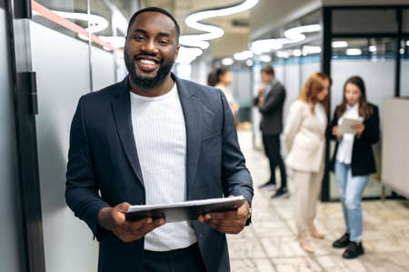 Handsome successful businessman in formal stylish suit is standing in office hall, smiling. Attractive african american male employee looking at the camera, hold tablet in arms