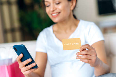 Pregnant woman in a white t-shirt sit on the couch, holds a credit card and a smartphone in hand, makes purchases online, buys clothes and toys for the future baby, online shopping Archivio Fotografico