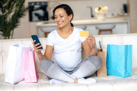 Pregnant woman in a white t-shirt sit on the couch, holds a credit card and a smartphone in hand, makes purchases online, buys clothes and toys for the future baby, packages