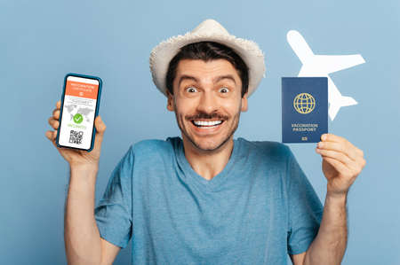 Excited happy caucasian guy in a hat, holds a passport and small airplane and smartphone, at a screen an electronic certificate of vaccination, a long-awaited vacation,blue isolated background