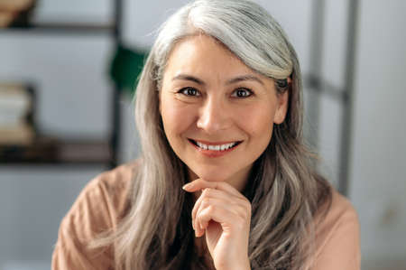 Close-up portrait of a beautiful successful mature asian business woman, self-confident gray haired lady in casual stylish wear, looking directly at the camera with friendly smile