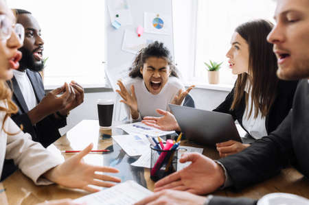 Unsuccessful briefing meeting. Tired multiracial colleagues are argue, having a work troubles, failed project or deal. African american female boss is stressed out and screaming