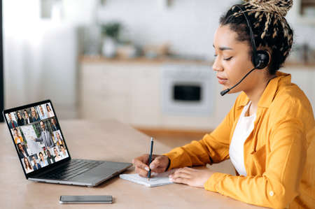 Online webinar, business meeting. Side view of african american woman, communicates with business colleagues by video call uses laptop, takes notes, multiracial coworkers on laptop screen, brainstorm