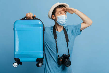 Joyful traveler in a hat and medical mask, dressed in blue t-shirt, holds a blue suitcase, with photo camera, looks into the distance, happy about of a long-awaited vacation, isolated blue background
