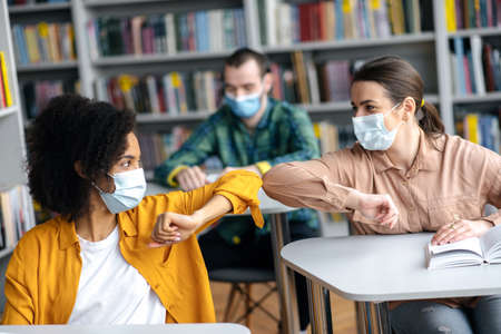 Two female student friends wearing protective face masks greeting each other bumping elbows while sitting at university library, healthcare concept, precautions, new normal Standard-Bild