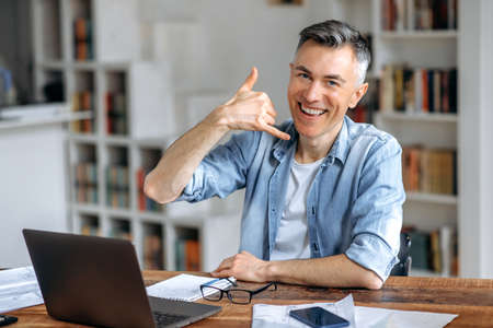 Friendly sociable confident middle aged gray-haired Caucasian male freelancer, in stylish clothes, works remotely at a laptop, shows the call me gesture, looks at the camera, smiles