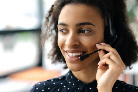 Close-up headshot of pleasant charming young african american curly haired woman in headset and stylish shirt, female call center worker or support operator, looking to the side, smiling friendly