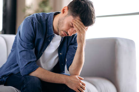 Upset sick stressed young caucasian man in casual clothes sits on sofa in the living room, bending over, massaging his head, suffering from pain, migraine, closing his eyes, needs treatment and rest