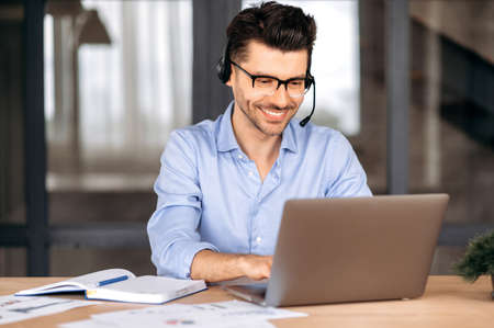 Happy confident caucasian man wearing glasses and headset, manager, freelancer or consultant, sitting in office, using laptop, chatting with client via video conference, typing on keyboard, smiling Banque d'images