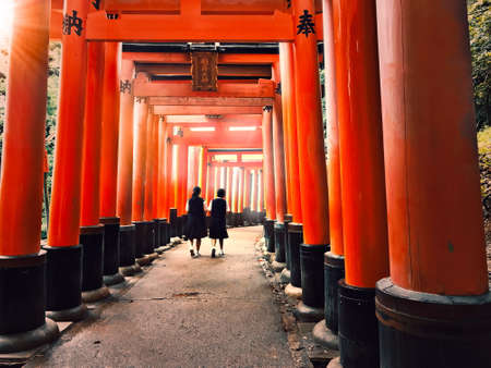 Pathway underneath red torii gates leading to a Japanese shrine Imagens