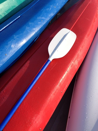 Paddle resting on a bright red kayak with other brightly color kayaks
