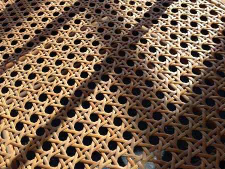 Rotan geweven zitting van de stoel in het zonlicht met schaduwen van de stoel terug te treden