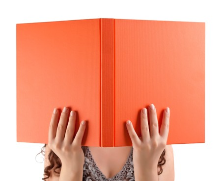 Young student holding book in front of her face. photo
