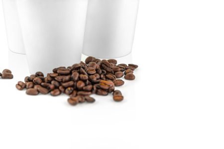 Close up set of white take-out coffee cups and coffee beans on white background