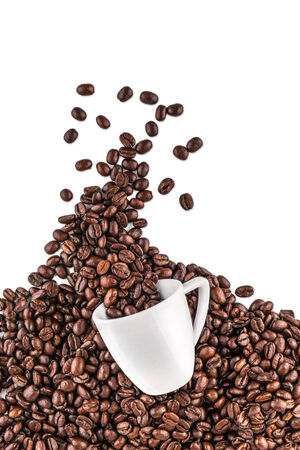 Spilled coffee beans from coffee cup on white background photo