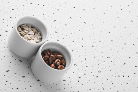 Set of saucers filled with coffee beans and sweet candy on white background Stock Photo