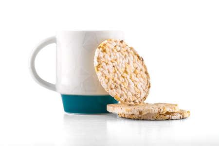 Coffee mug with rice waffles on white background