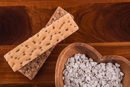 Brown and creamy crispbreads with bowl of candies on wooden table Stock Photo